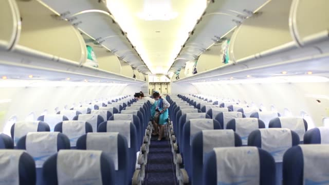 flight attendants stow luggage in the aisles of a bangkok airways co airbus sas a319 aircraft at hong kong international airport in hong kong, china,... - passagier stock-videos und b-roll-filmmaterial