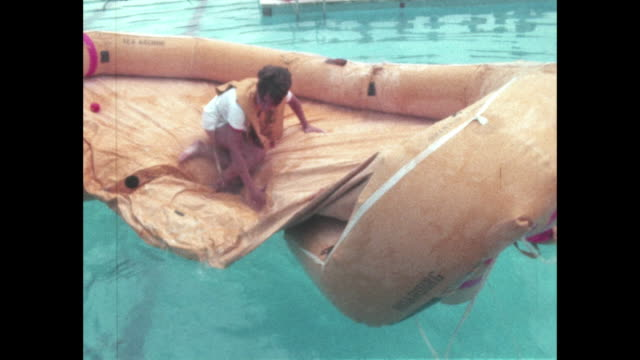 flight attendants train for airplane landing in water emergency life raft inflated in swimming pool during training session - air stewardess stock videos & royalty-free footage