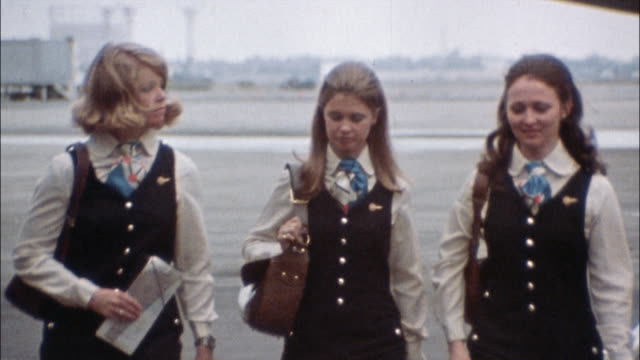 flight attendants wearing uniforms pass a parked airplane. - uniform stock videos & royalty-free footage