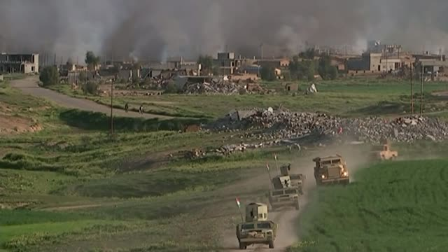 vídeos de stock, filmes e b-roll de flight ban after kurdish freedom vote tx wide shot military vehicles towards smoke rising above village in background following battle against... - iraque