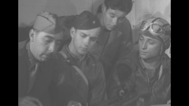 Flight crew members one still dressed in flight gear answer questions in debriefing after their bombing mission over Europe gunner and bombardier...