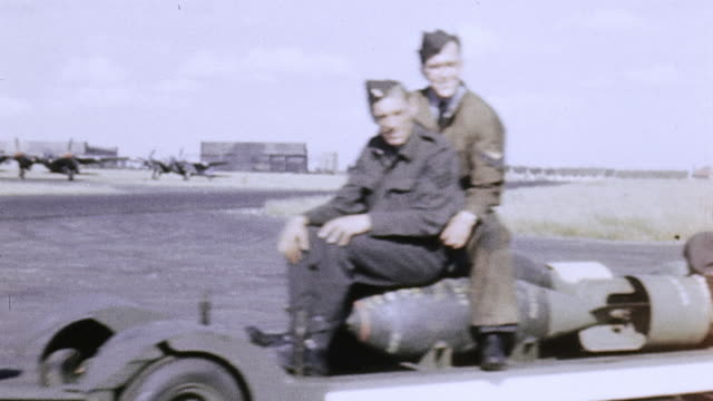 ts raf flight crew riding on tractor and towed trailers carrying bombs the last blockbuster with sign reading 'have this one on me' and lancaster... - rimorchiare video stock e b–roll