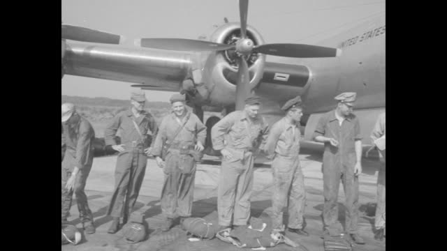 vídeos de stock, filmes e b-roll de flight crew standing in line on tarmac next to plane, parachutes lying on ground in front of them, one man next to crew writing on paper on clipboard... - pista de aterrizagem