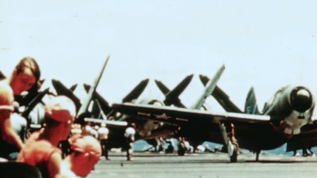 Flight crew turning prop of TBF Avenger by hand and SB2C Helldiver taking off leaving aircraft carrier behind / Philippines