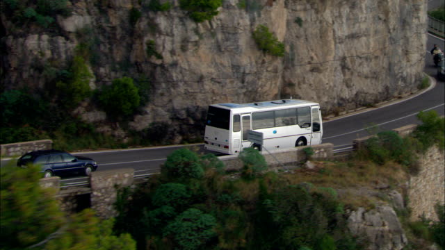 flight following bus on amalfi coast road  - aerial view - campania, provincia di salerno, positano, italy - tour bus stock videos and b-roll footage
