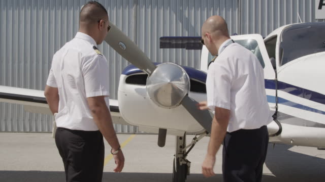 flight instructor and trainee pilot during pre flight inspection of aircraft; instructor demonstrating check of propeller blades, air intakes and exhaust, red r3d 4k - propeller video stock e b–roll
