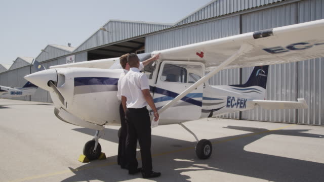 flight instructor and trainee pilot during pre flight inspection of aircraft; instructor demonstrating check of cabin air intake, pitot tube and cover, stall warning switch and tiedowns, RED R3D 4K