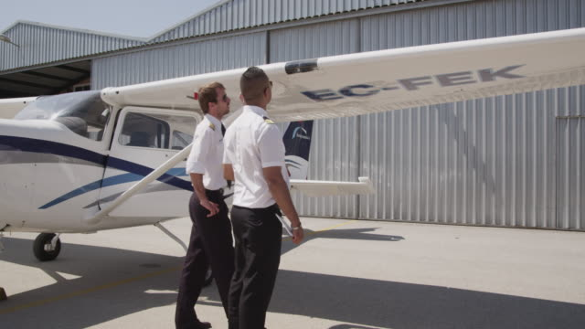 flight instructor and trainee pilot during pre flight inspection of aircraft; instructor demonstrating check of landing and taxi light covers, wing leading edge, ailerons and hinges, RED R3D 4K