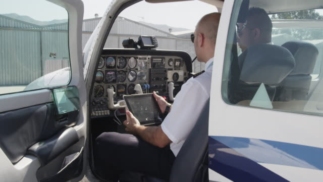 flight instructor and trainee pilot during pre flight setting up of instruments in cockpit using tablet computer running the checklist, red r3d 4k - pilot stock videos and b-roll footage