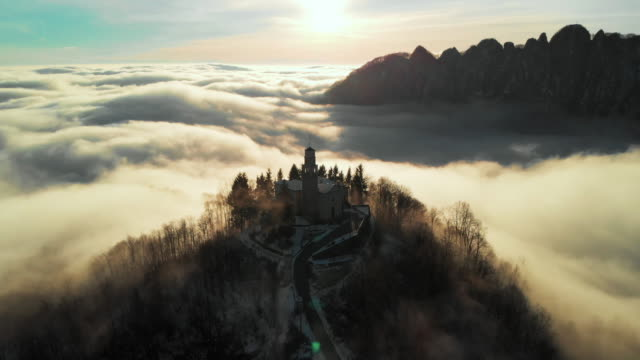 flight over a church on top of the hill during the sunrise surrounded by clouds in the dolomites, veneto, padan plain. - idyllic video stock e b–roll