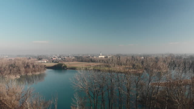 flight over a lake with birds and trees towards a village and a church during a sunny clear sky day - sunny video stock e b–roll