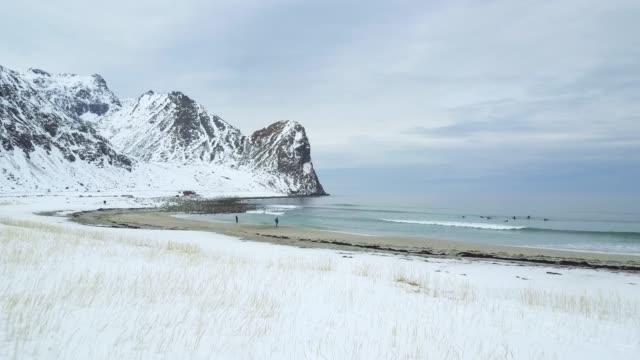 Vlucht over een besneeuwde strand naar een blauwe golvende Oceaan in Lofoten, Noorwegen.