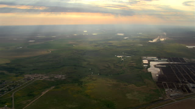 flight over a texas landscape where slanting evening rays sparkle on pools of water - prärie stock-videos und b-roll-filmmaterial