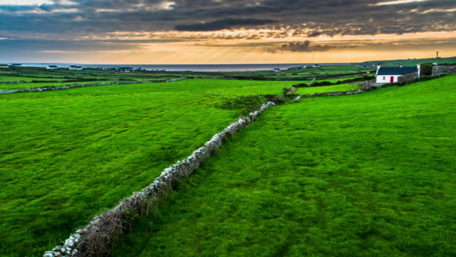 Flight over an old stone wall in rural landscape in Ireland