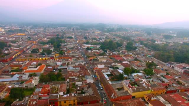 flight over city of antigua with view to agua volcano, guatemala - agua点の映像素材/bロール