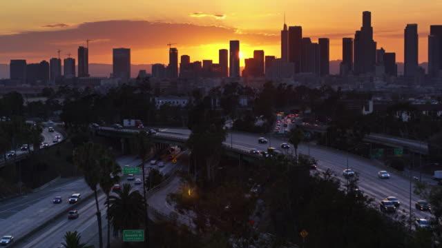 Flight Over East Los Angeles Interchange with DTLA Skyline at Dusk
