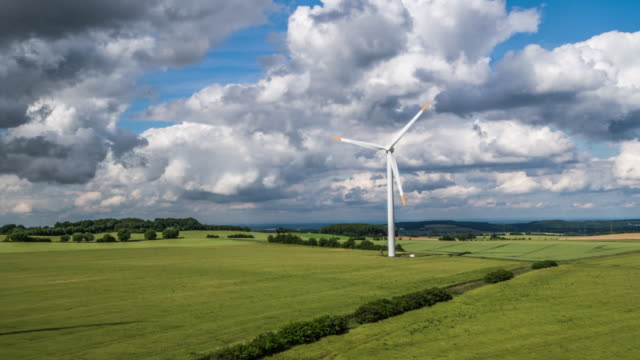 Flight over green fields with Wind Turbine