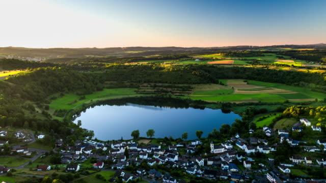 Flight over idyllic landscape with volcanic crater lake Schalkenmehrener Maar in Germany