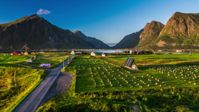 Flight over idyllic village in fjord landscape, Lofoten Islands - Norway
