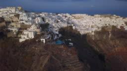 Flight over of Firostefani and Imerovigli  town at sunset, Santorini island, Greece
