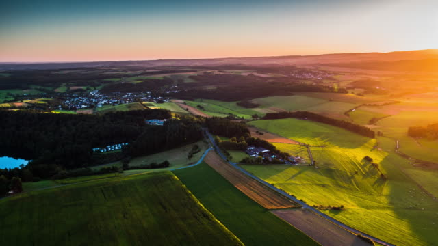 Flight over rural landscape in beautiful sunset light in Germany