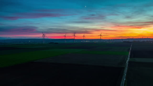 Flight over rural landscape with wind turbines under dramatic sunset sky