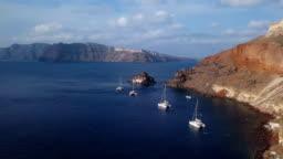 Flight over small island church (Nisis Agios Nikolaos) near Oia town, Santorini island, Greece
