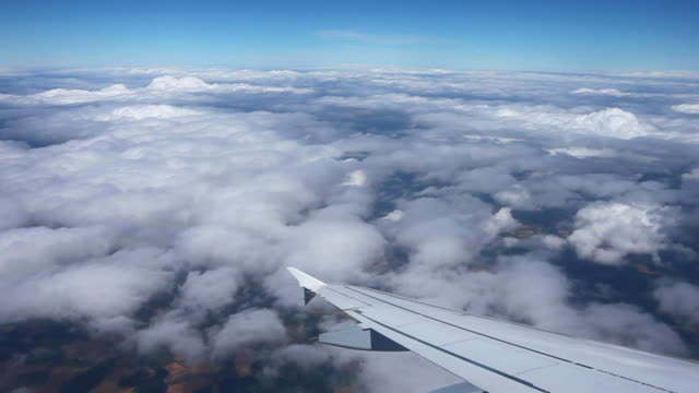 aerial pov flight over the clouds viewed from passenger point of view - aircraft wing stock videos & royalty-free footage