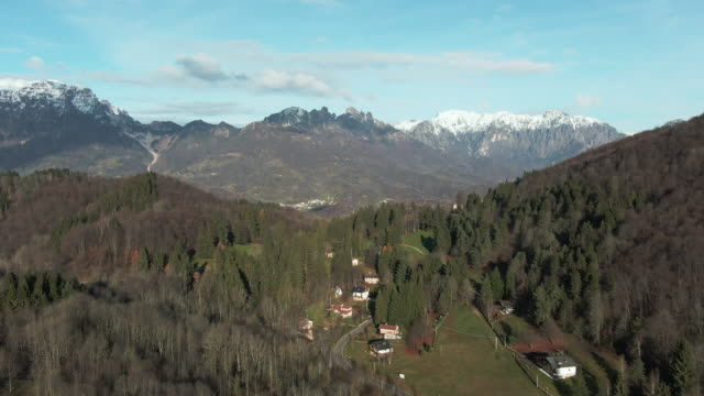 flight over the mountains and the valley below on a sunny day with clouds and pine trees in the dolomites mountains, veneto, italy. - valley stock videos & royalty-free footage