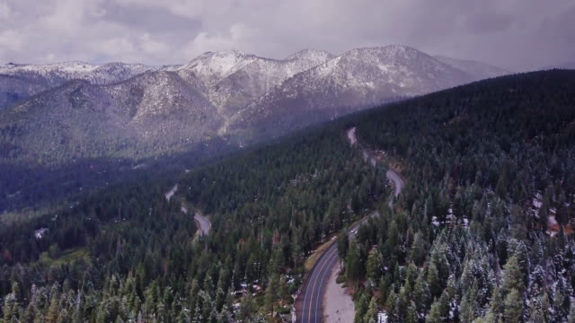 flight over two roads in sierra nevada forest during snowfall - californian sierra nevada stock videos and b-roll footage