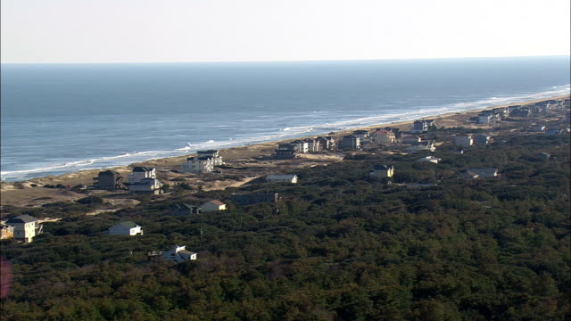 flight past beach-side houses  - aerial view - north carolina,  currituck county,  united states - north carolina beach stock videos & royalty-free footage