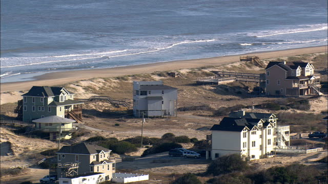flight past houses in sand dunes  - aerial view - north carolina,  currituck county,  united states - sand dune stock videos & royalty-free footage