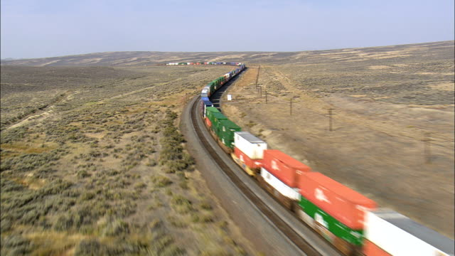 Flight Past Long Freight Train Waiting At A Signal  - Aerial View - Wyoming, Carbon County, United States