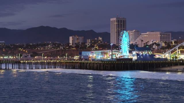 flight past santa monica pier at night - santa monica city stock videos & royalty-free footage