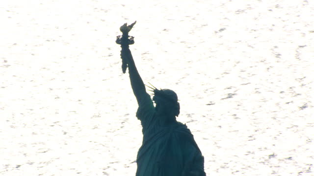 flight past silhouetted statue of liberty. shot in 2003. - artbeats stock videos & royalty-free footage
