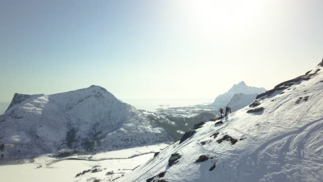 flight towards snowboarders standing on a mountain ridge in lofoten, norway. - avalanche stock videos and b-roll footage