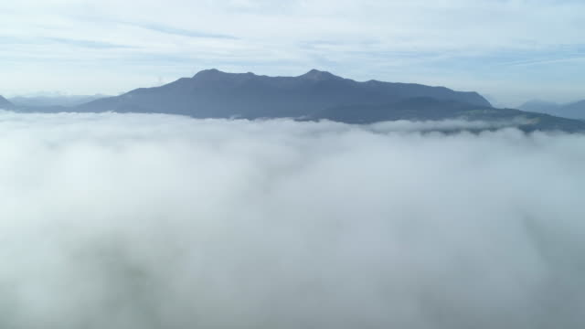 stockvideo's en b-roll-footage met flight with aerial view over fog at morning. in distant are the bavarian alps. loisach moor or loisach-kochelsee-moor, blaues land region, bavarian alps, upper bavaria, bavaria, germany, europe, european alps. - bavarian alps