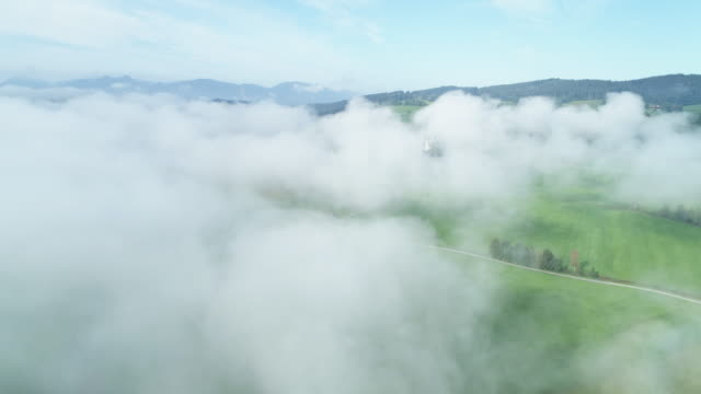 stockvideo's en b-roll-footage met flight with aerial view to landscape with meadows and trees with fog at morning. in distant are the bavarian alps. loisach moor or loisach-kochelsee-moor, blaues land region, bavarian alps, upper bavaria, bavaria, germany, europe, european alps. - bavarian alps