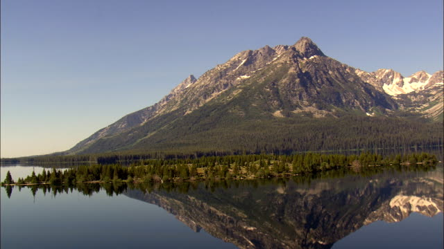 flight with reflections of teton range in leight lake  - aerial view - wyoming,  teton county,  helicopter filming,  aerial video,  cineflex,  establishing shot,  united states - grand teton national park stock videos & royalty-free footage