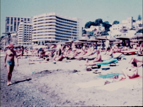 flights to european resorts fully booked despite recession; 1.7.1979 spain: ext crowded beach people on beach people sunbathing zoom in one oiling... - tourist resort stock videos & royalty-free footage