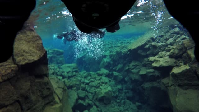 flippers propel snorkeler through crystal water between tectonic plates in iceland - tectonic stock videos & royalty-free footage