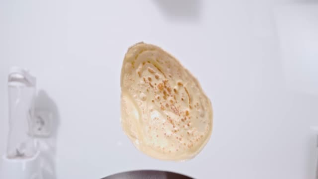 slo mo flipping a pancake - lanciare video stock e b–roll