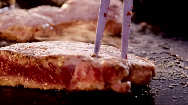 vídeos de stock e filmes b-roll de slo mo flipping a steak on a hot grill plate - utensílio