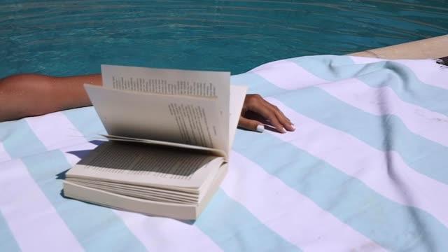 flipping-buch am pool - wisdom stock-videos und b-roll-filmmaterial
