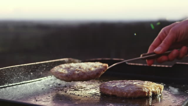 slo mo flipping burgers on a grill plate - hamburger stock videos & royalty-free footage