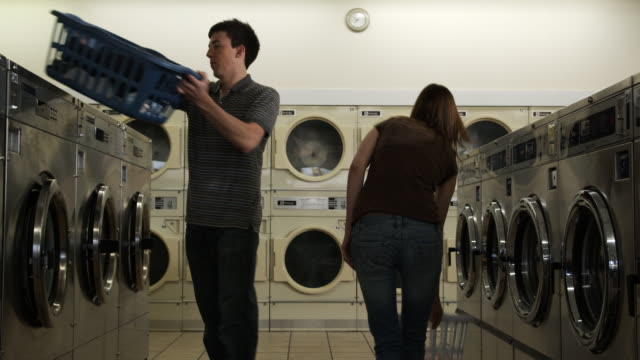 flirting at laundromat - launderette stock videos and b-roll footage