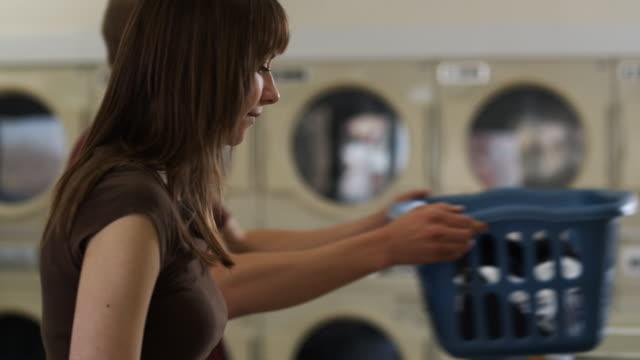 stockvideo's en b-roll-footage met flirting at laundromat - wasmand