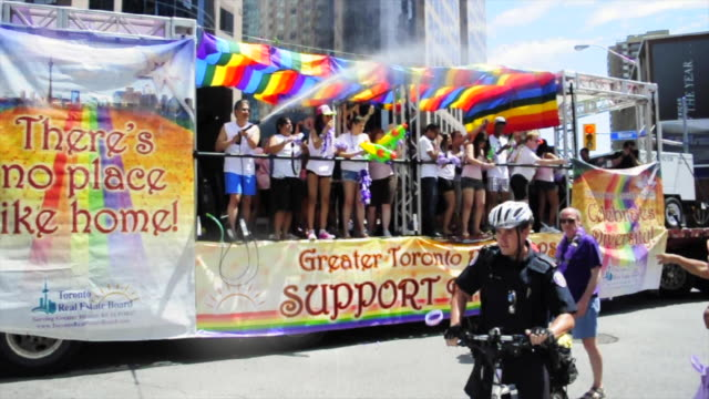 float of the real estate board celebrating diversity. the people on board use water guns to get the public wet. the gay pride parade is a traditional... - water pistol stock videos & royalty-free footage