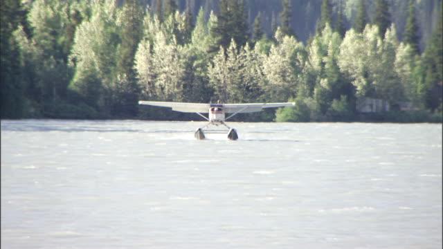 a float plane lands on a stream in an alaska wilderness area. - 水上飛行機点の映像素材/bロール