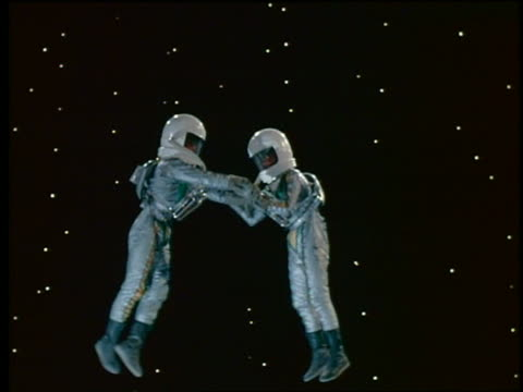 2 floating astronauts in spacesuits grabbing hands + waving at the camera